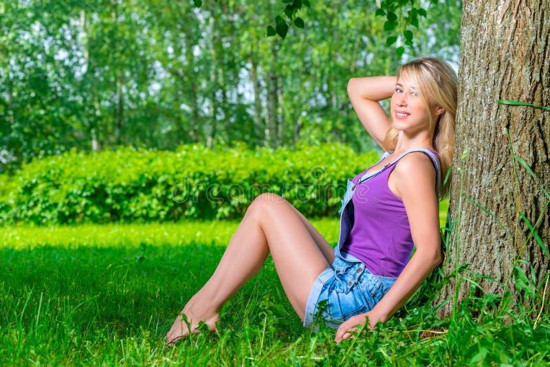 Mooie jonge blonde vrouwenzitting dichtbij de boom royalty-vrije stock foto's
