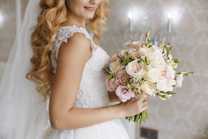 Mooie jonge blondebruid met modieus huwelijkskapsel in een witte modieuze kleding met een binnen boeket van bloemen stock fotografie