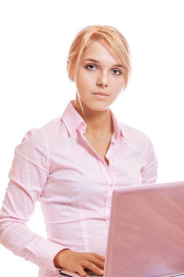 Mooie jonge blondevrouw die aan roze laptop werken stock foto's