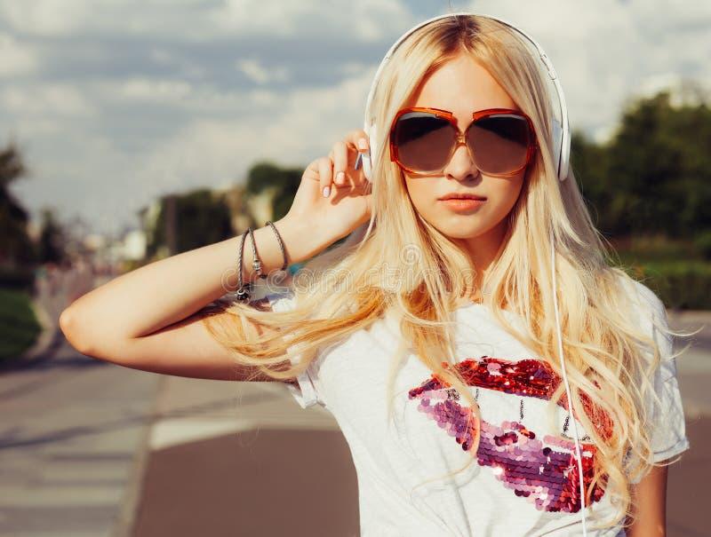 Mooie jonge blondevrouw die in uitstekende zonnebril aan muziek met hoofdtelefoons luisteren De gelukkige jonge zakken van de mei stock afbeelding