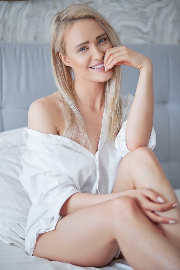 Mooie jonge blondevrouw die in wit overhemd bij camera glimlachen royalty-vrije stock foto's