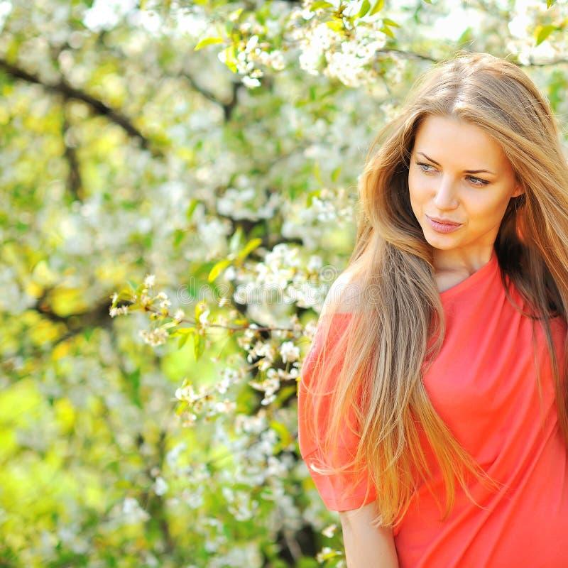Mooie jonge blondevrouw die zich dichtbij bloeiende boom bevinden - copys stock afbeeldingen