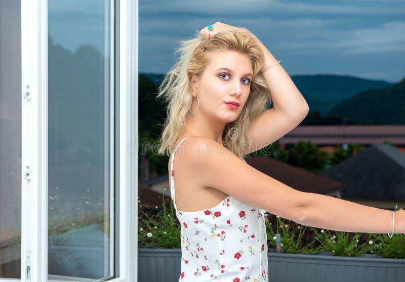 Mooie jonge blondevrouw die zich dichtbij het venster bevinden royalty-vrije stock afbeelding