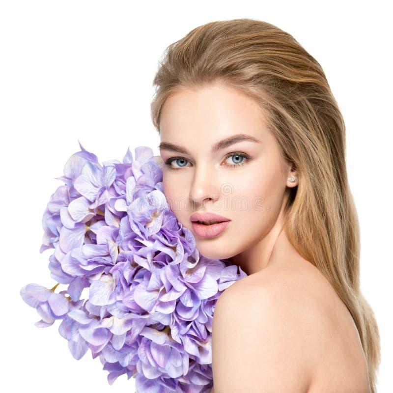 Mooie jonge blondevrouw met bloemen dichtbij gezicht stock fotografie
