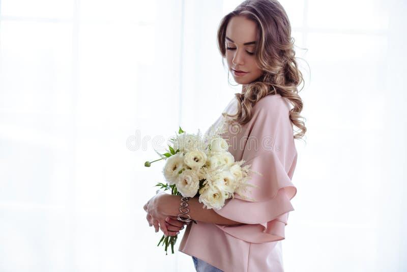 Mooie jonge blondevrouw met boeket van witte bloemen Portret van mooi blondemeisje in roze kleren stock afbeeldingen