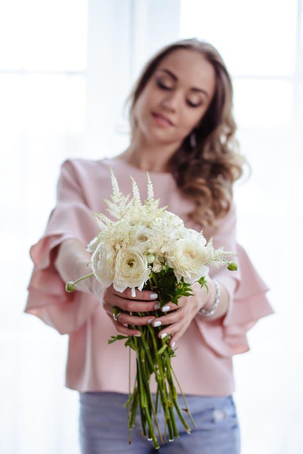 Mooie jonge blondevrouw met boeket van witte bloemen Portret van mooi blondemeisje in roze kleren royalty-vrije stock foto's