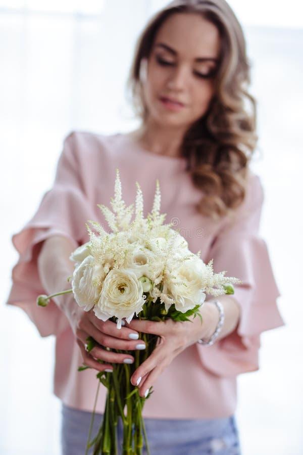Mooie jonge blondevrouw met boeket van witte bloemen Portret van mooi blondemeisje in roze kleren royalty-vrije stock fotografie