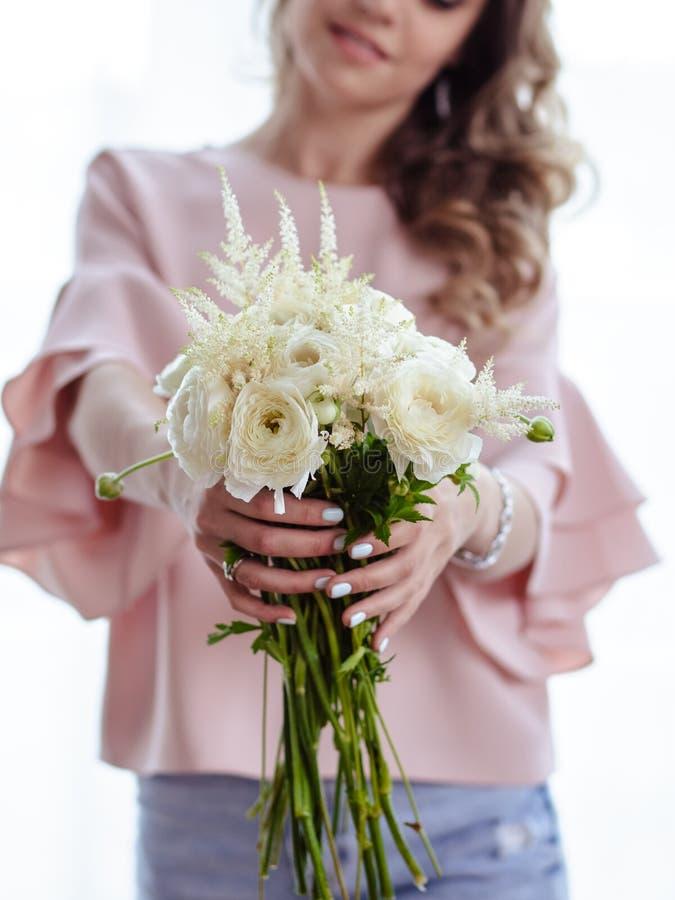 Mooie jonge blondevrouw met boeket van witte bloemen Portret van mooi blondemeisje in roze kleren stock foto