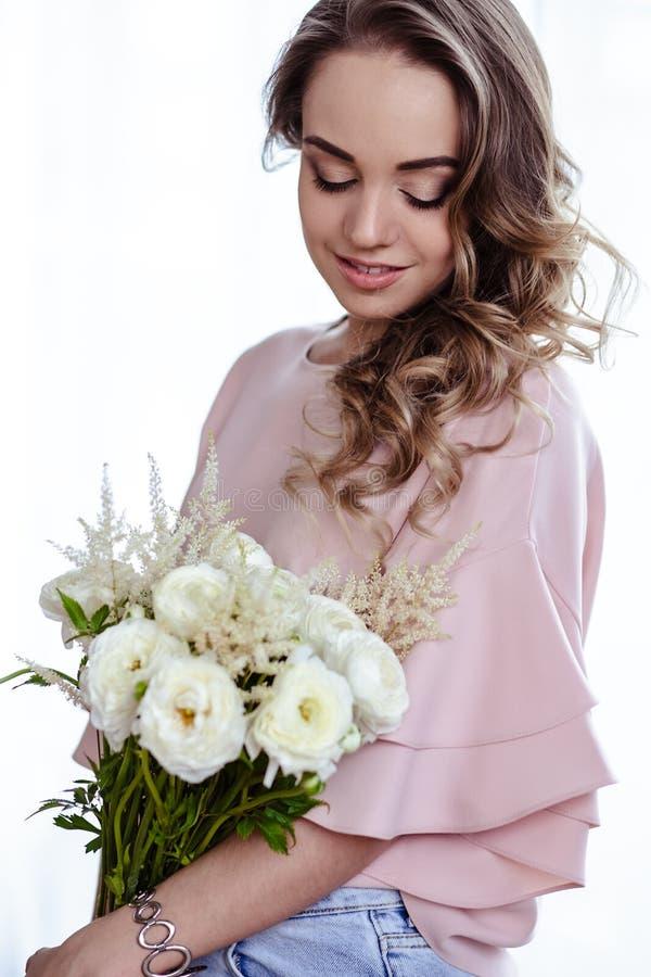 Mooie jonge blondevrouw met boeket van witte bloemen Portret van mooi blondemeisje in roze kleren stock fotografie