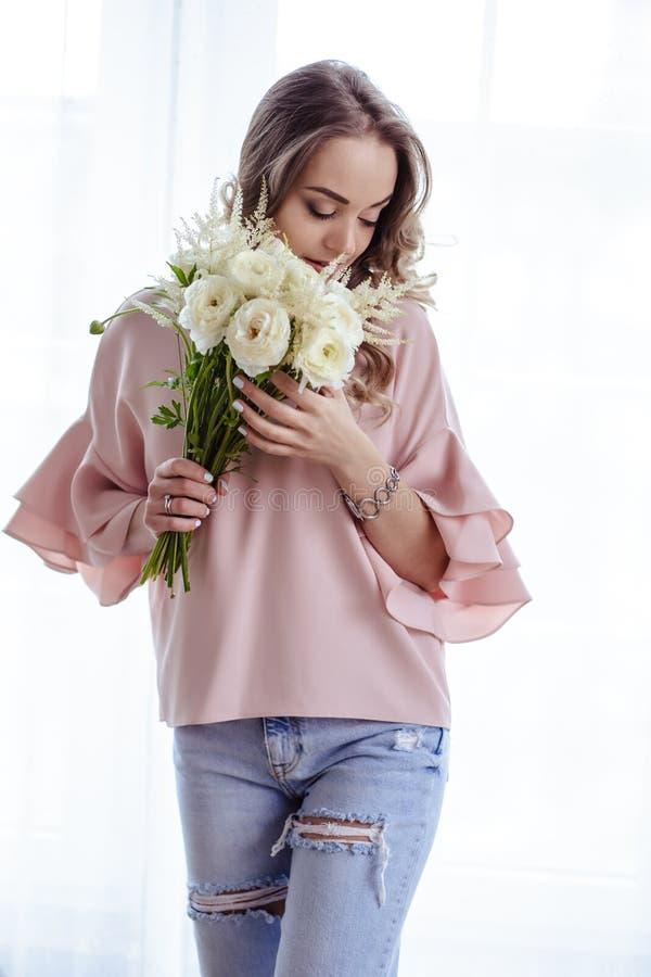 Mooie jonge blondevrouw met boeket van witte bloemen Portret van mooi blondemeisje in roze kleren royalty-vrije stock afbeelding