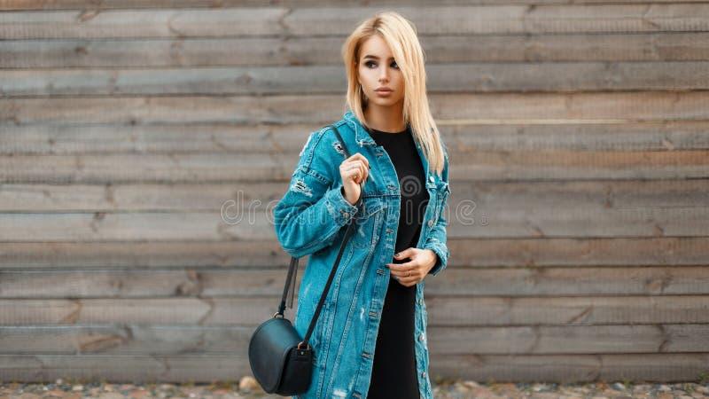 Mooie jonge blondevrouw met een handtas in een denimjasje royalty-vrije stock fotografie