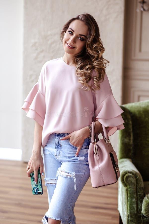 Mooie jonge blondevrouw met lichtrose handtas en mobiele telefoon royalty-vrije stock afbeelding