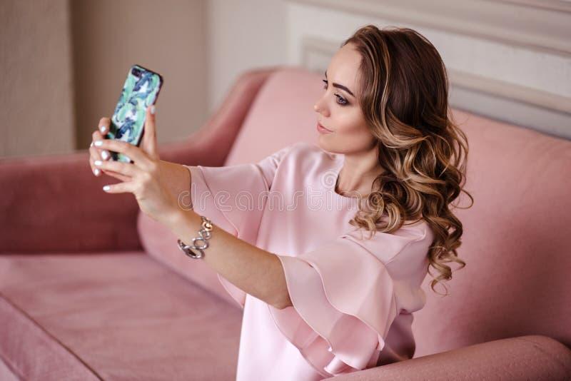 Mooie jonge blondevrouw met mobiele telefoon Portret van mooi blondemeisje in vrijetijdskleding stock fotografie