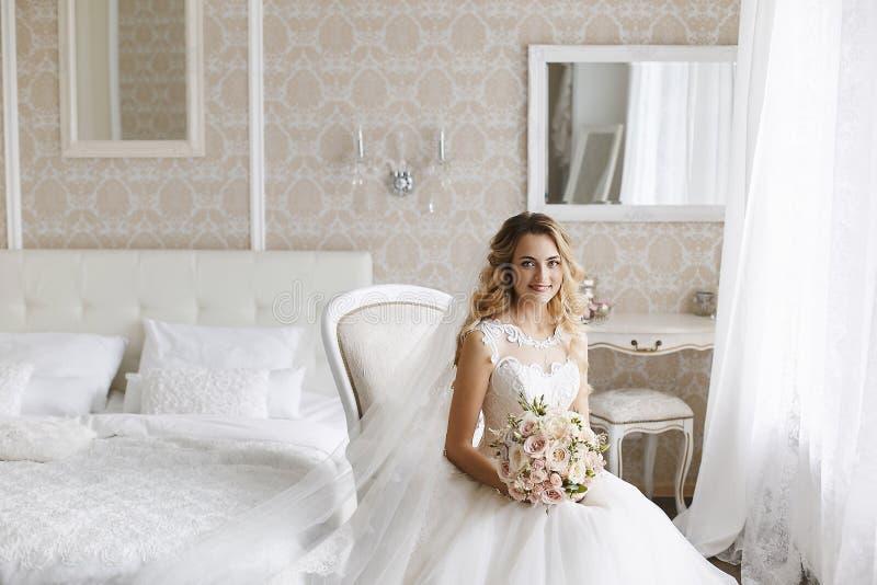 Mooie jonge blondevrouw met modieus huwelijkskapsel in een witte modieuze kleding die een boeket van bloemen houden royalty-vrije stock foto's
