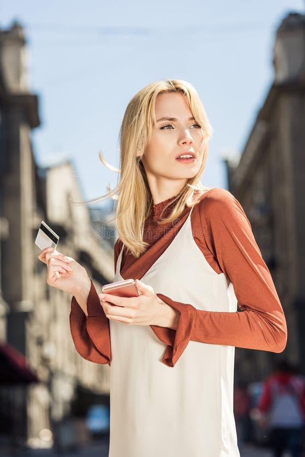 mooie jonge blondevrouw met smartphone en creditcard die weg eruit zien stock foto's