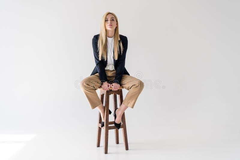 mooie jonge blondevrouw in modieuze kleren die op kruk zitten en camera bekijken royalty-vrije stock foto