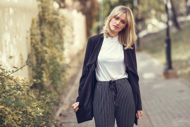 Mooie jonge blondevrouw op stedelijke achtergrond stock foto's