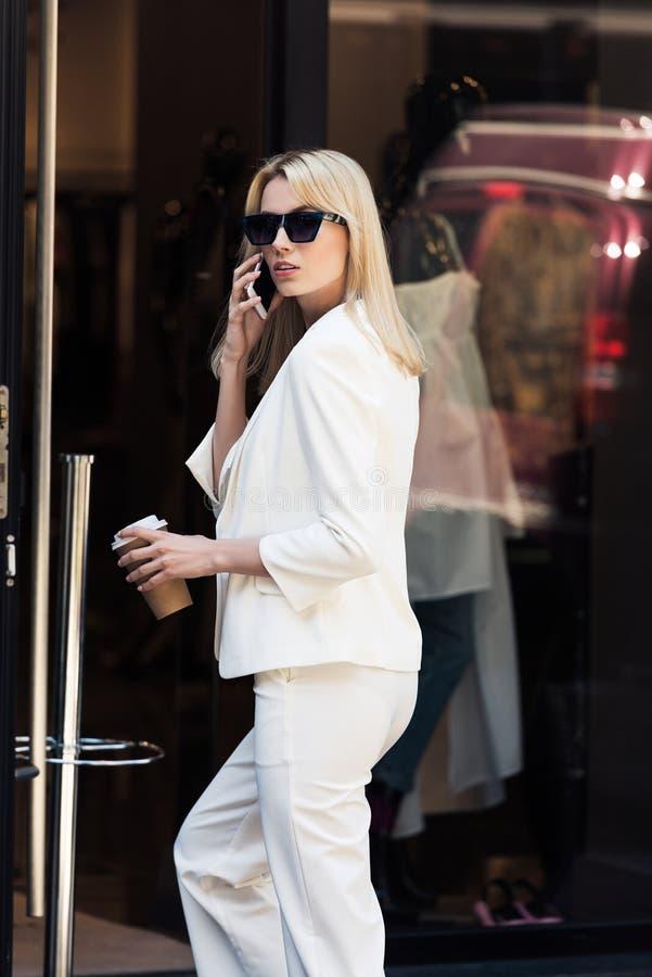 mooie jonge blondevrouw in zonnebril die door smartphone en het drinken koffie spreken royalty-vrije stock fotografie
