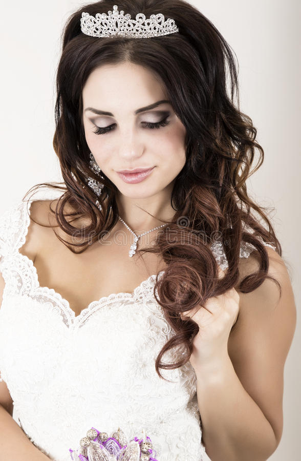 Mooie jonge bruid die witte huwelijkskleding met professionele samenstelling dragen stock foto