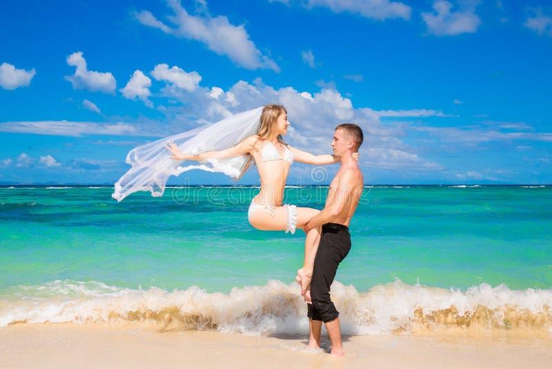 Mooie jonge bruid in een witte bikini, een sluier en een kouseband op haar stock foto