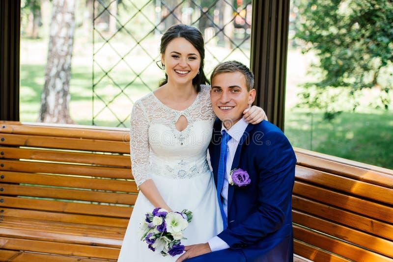 Mooie jonge bruid en bruidegomzitting op een bank en holdingshanden royalty-vrije stock afbeeldingen