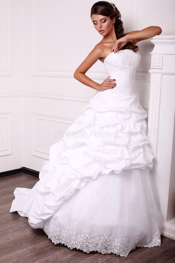 Mooie jonge bruid met donker haar in huwelijkskleding stock foto's