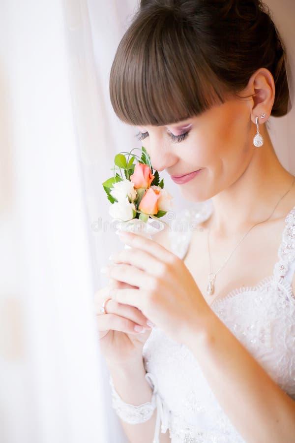 Mooie jonge bruid met huwelijksmake-up en kapsel in bedro stock foto