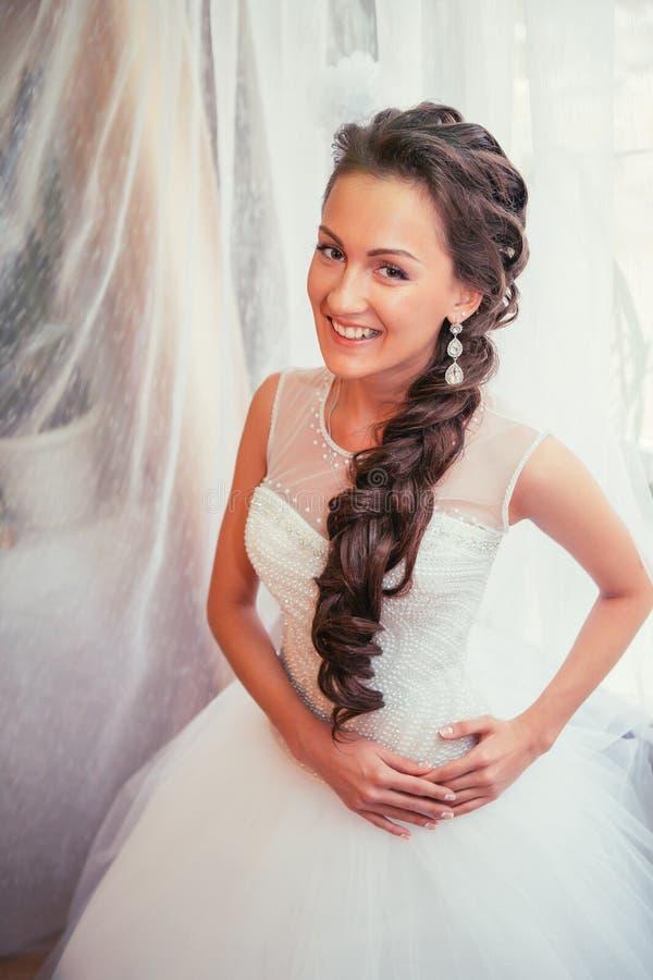 Mooie jonge bruid met huwelijksmake-up en kapsel in slaapkamer, de definitieve voorbereiding van de jonggehuwdevrouw voor huwelij royalty-vrije stock foto