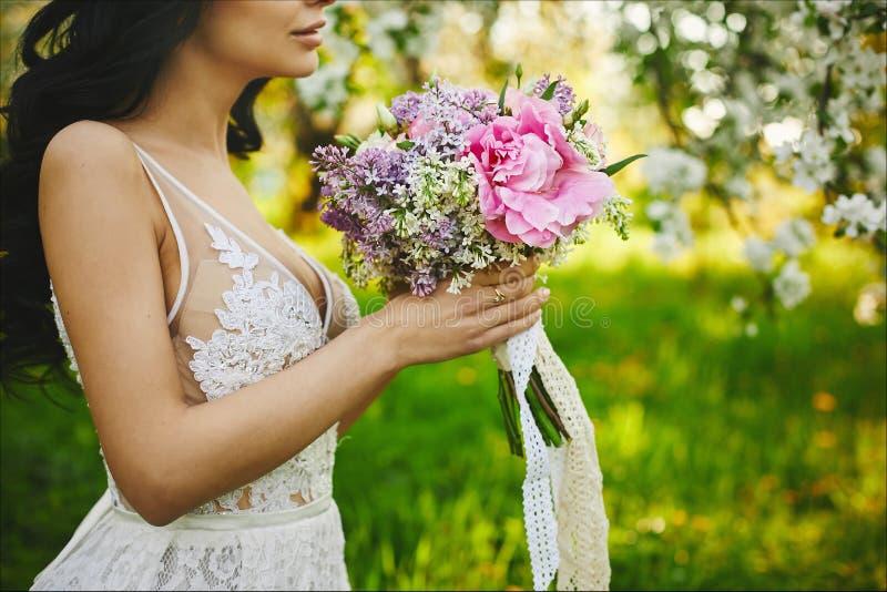 Mooie jonge bruid, model donkerbruin meisje in witte kleding, met bloemen in haar handen, die in openlucht stellen stock fotografie