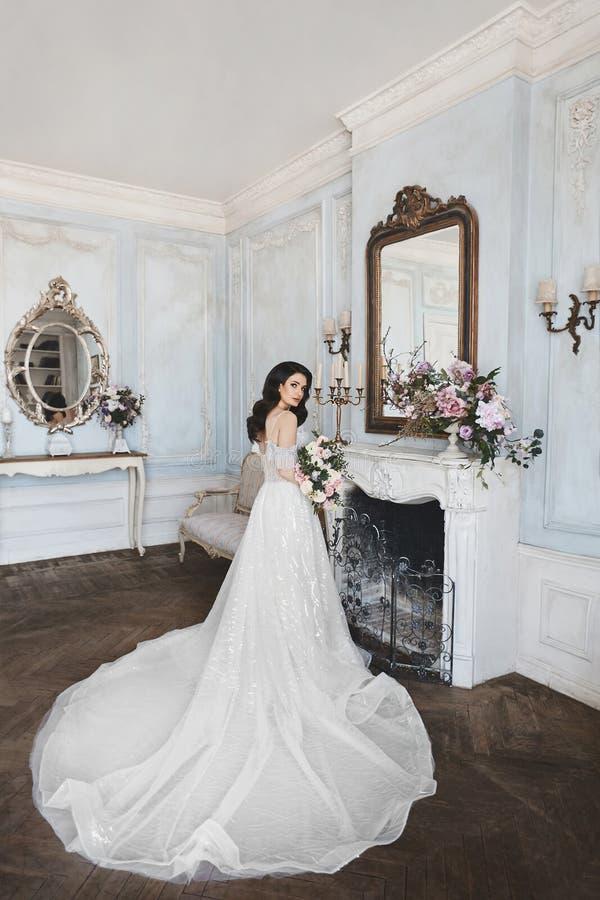Mooie jonge bruid, sexy en sensueel donkerbruin modelmeisje in modieuze en modieuze huwelijkskleding met naakte schouders die w s royalty-vrije stock afbeeldingen
