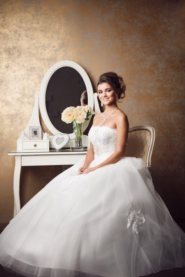 Mooie jonge bruidzitting dichtbij spiegel stock afbeeldingen