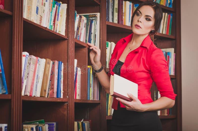 Mooie jonge bruin-haired vrouw in bureaukledij statusnea royalty-vrije stock afbeeldingen