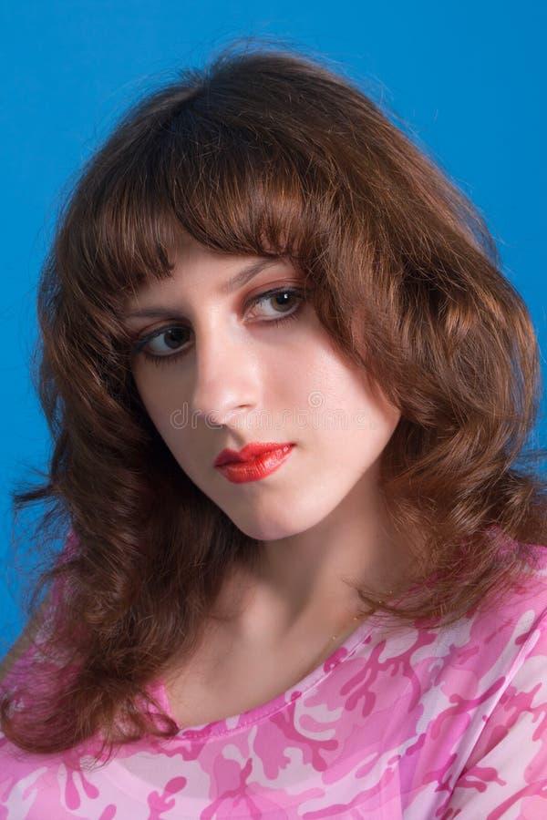 Mooie jonge brunette in een roze kleding op een blauwe achtergrond stock fotografie