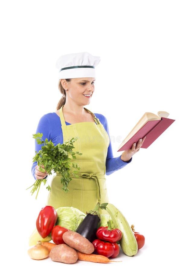 Mooie jonge chef-kokvrouw die een bos van peterselie houden en readin stock afbeelding
