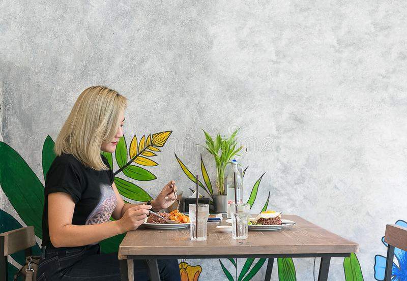 Mooie jonge dame alleen in restaurant royalty-vrije stock fotografie