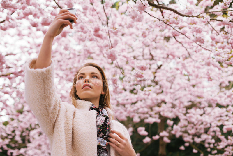 Mooie jonge dame die aard met haar mobiele telefoon fotograferen stock afbeelding
