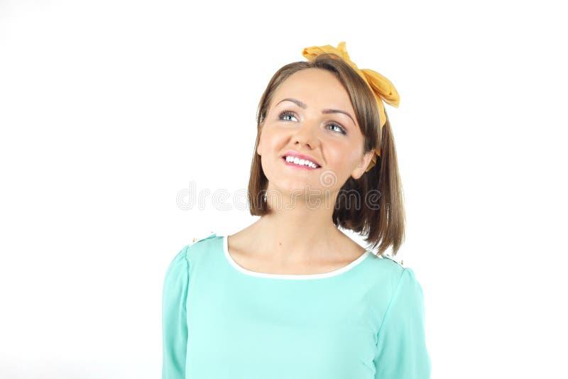 Mooie jonge dame die wit bloemenboeket houden die het gele boog stellen op een witte achtergrond in studio dragen stock foto