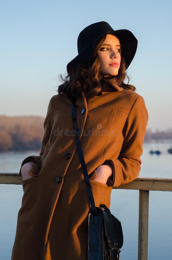 Mooie jonge dame die zich op brug het letten op de herfstzonsondergang bevinden royalty-vrije stock fotografie