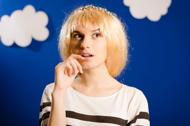 Mooie jonge dame in gouden pruik op document wolken stock foto's