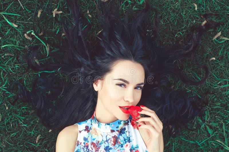 Mooie jonge dame met aardbei in mond stock afbeeldingen