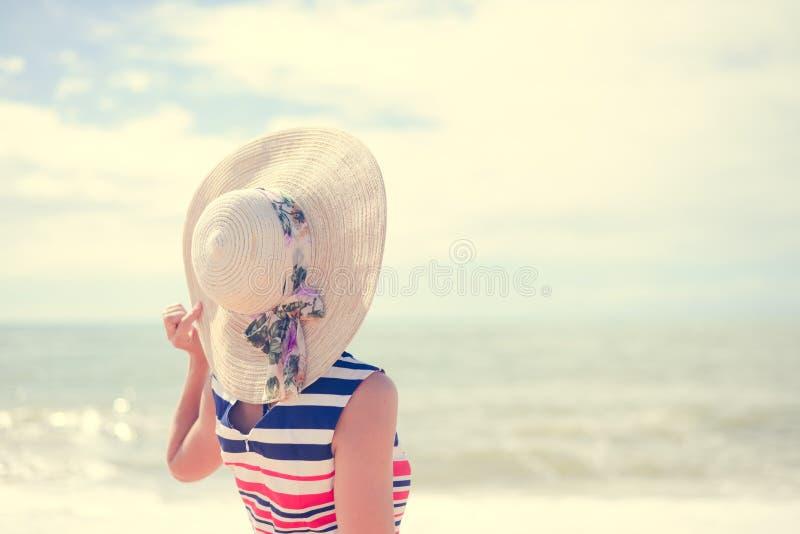 Mooie jonge dame in strohoed die op zonnig rusten royalty-vrije stock afbeelding