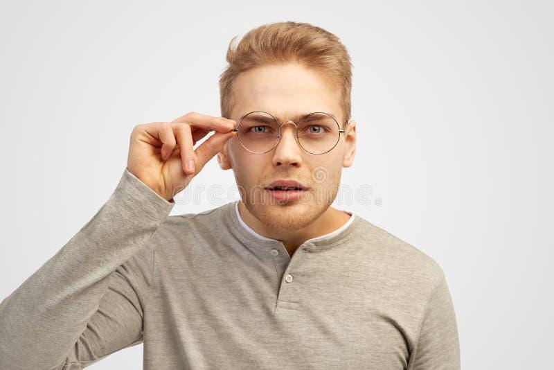 Mooie jonge de holdingsglazen van de blondekerel en het loensen het proberen om de inschrijving voor hem te lezen stock foto's