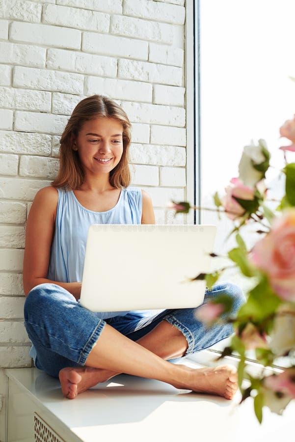 Mooie jonge de koffiekop van de meisjesholding en het houden van benen gekruist royalty-vrije stock afbeeldingen