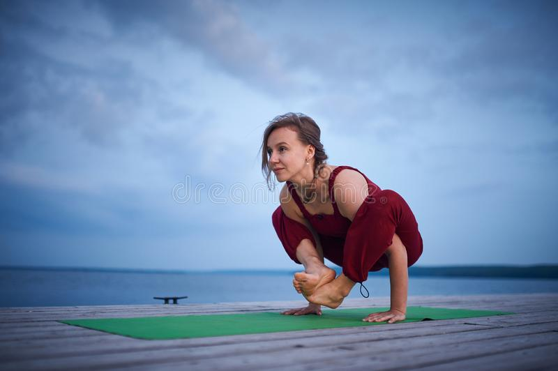 Mooie jonge de yogaasana Malasana van vrouwenpraktijken - de Slinger stelt op het houten dek dichtbij het meer stock foto