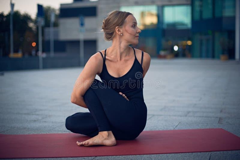 Mooie jonge de yogaasana Marichiasana 4 van vrouwenpraktijken - de salie stelt in openlucht tegen de achtergrond van een moderne  royalty-vrije stock fotografie