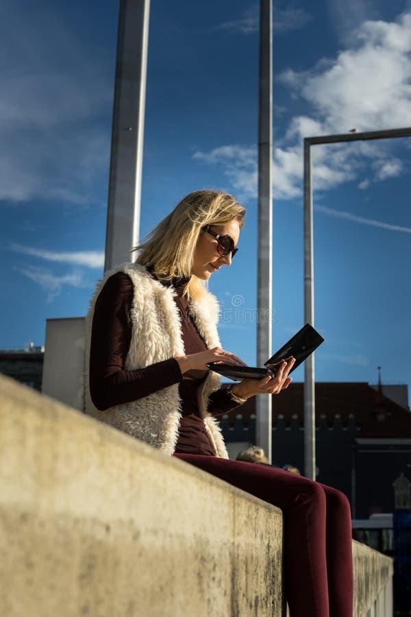 Mooie Jonge Dichte Omhooggaand van de Vrouw Het blondemeisje zit op stappen die buiten een bureau, een tablet houden Wijfje met n royalty-vrije stock foto