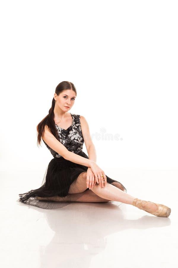 Mooie jonge die ballerina, op witte achtergrond wordt geïsoleerd In pointes en zwarte ballettutu Zit op de streng, toont verschil royalty-vrije stock foto's