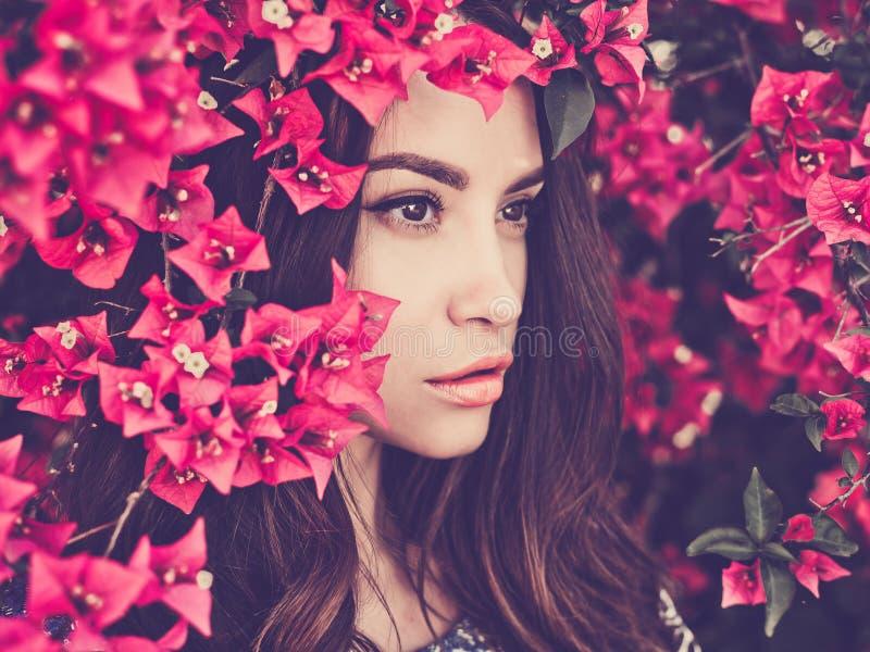 Mooie jonge die vrouw door bloemen wordt omringd stock foto