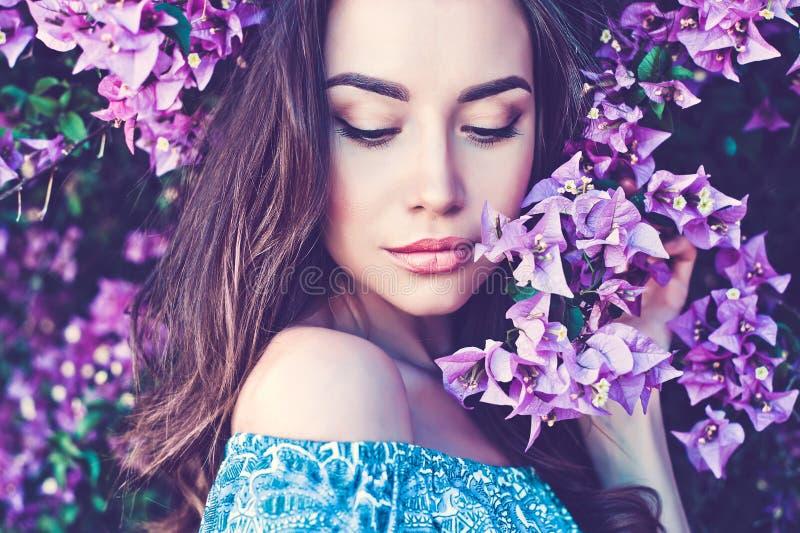 Mooie jonge die vrouw door bloemen wordt omringd stock afbeeldingen