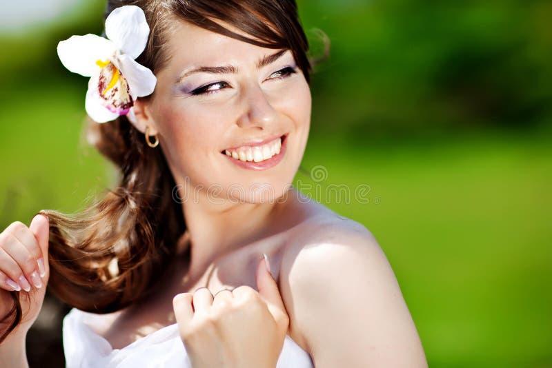 Mooie jonge donkerbruine bruid met bloem in haar haar stock foto's